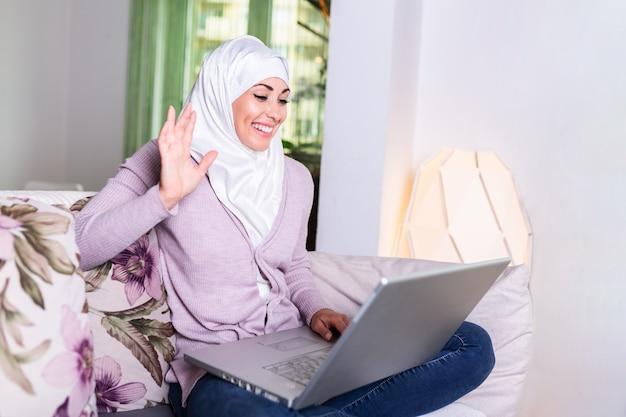 Junge muslimische frau, die videoanruf über laptop zu hause hat.