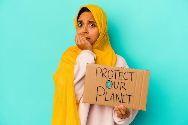 Junge muslimische frau hält einen schutz unseres planeten isoliert auf blaue wand beißen fingernägel, nervös und sehr ängstlich