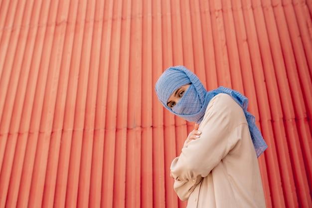 Junge muslimische frau im hijab, die ihre arme auf brust und rote wand kreuzt