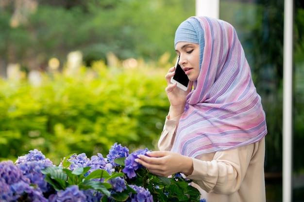 Junge muslimische frau im hijab, die mit jemandem auf smartphone spricht, während sie mit blumenhülle durch blumenbeet steht
