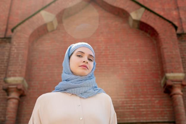 Junge muslimische frau im hijab-stehen der wand des orientalischen palastes