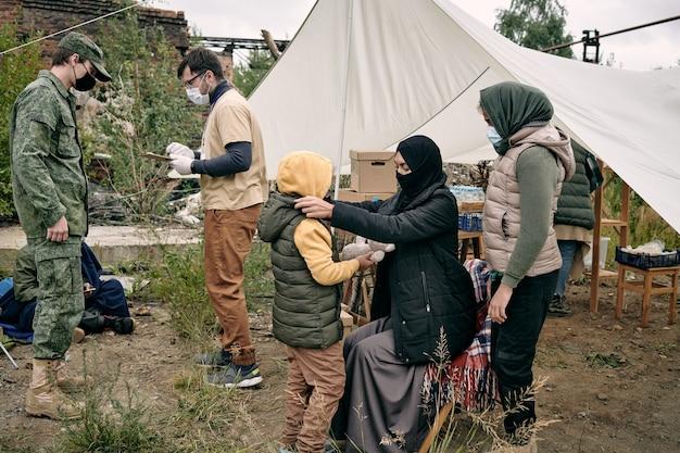 Junge muslimische frau in schutzmaske beim anziehen ihrer tochter