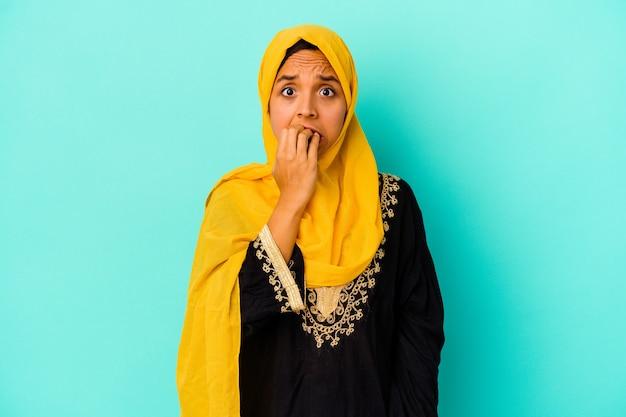 Junge muslimische frau isoliert auf blauer wand beißen fingernägel, nervös und sehr ängstlich