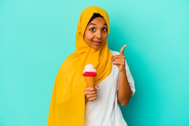 Junge muslimische frau isst ein eis isoliert auf blauem hintergrund und hat eine idee, inspirationskonzept.