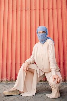 Junge muslimische frau mit hijab versteckt ihr gesicht und freizeitkleidung, die gegen rote wand hockt