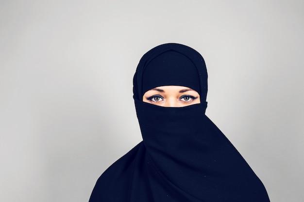 Junge muslimische frau mit niqab auf grauem hintergrund