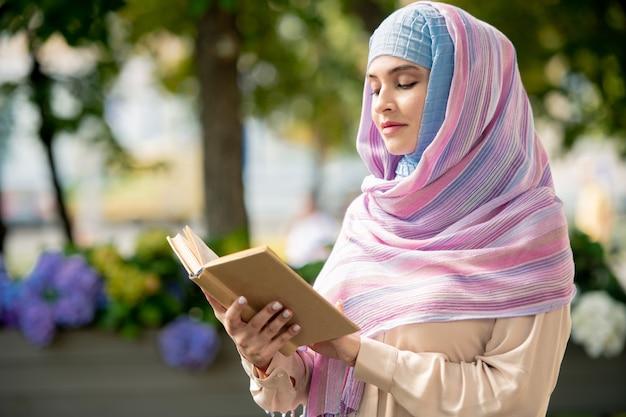 Junge muslimische frau mit offenem buch, das geschichten oder roman liest, während zeit im park verbringt