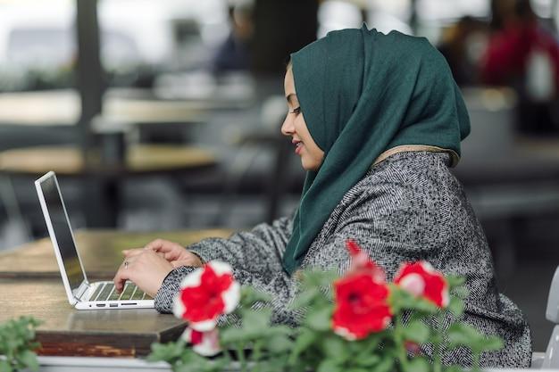 Junge muslimische frau sitzt in einem straßencafé und schaut in einen laptop