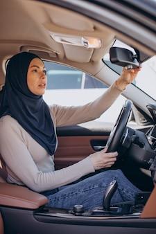 Junge muslimische frau sitzt in ihrem auto und schaut in den spiegel