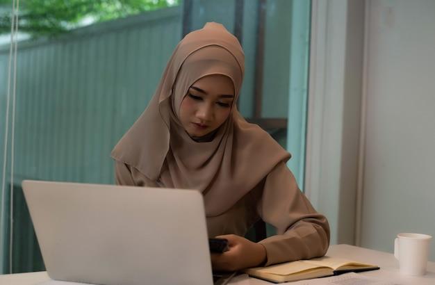 Junge muslimische geschäftsfrau, die arbeit, ernstes gefühl, büro beschäftigt zeit tut