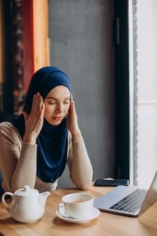 Junge muslimische geschäftsfrau, die kopfschmerzen hat und online an einem computer arbeitet