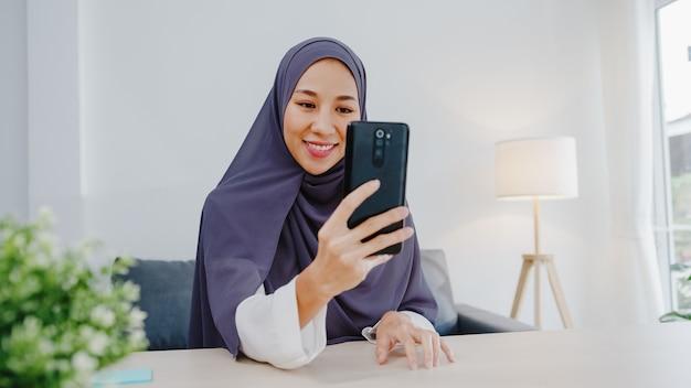 Junge muslimische geschäftsfrau, die smartphone verwendet, spricht mit einem freund per videochat-brainstorming-online-meeting, während sie von zu hause aus im wohnzimmer arbeitet.