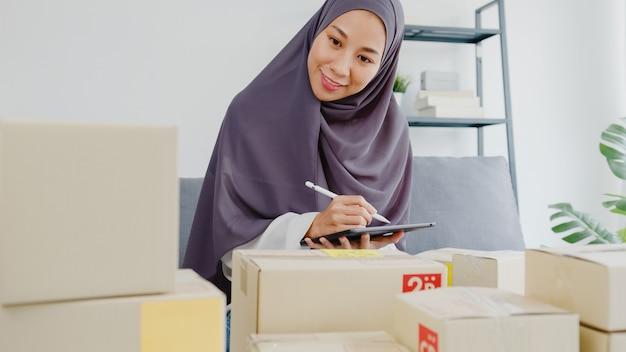 Junge muslimische geschäftsfrau prüft die produktbestellung auf lager und speichert sie auf tablet-computer-arbeit im home office.