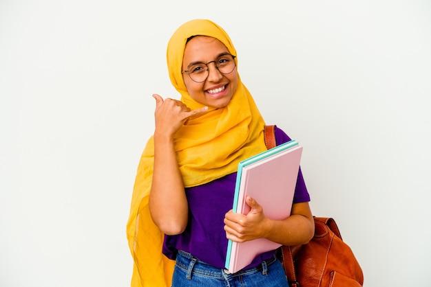 Junge muslimische studentin trägt einen hijab isoliert auf weißem hintergrund, der eine handy-anrufgeste mit den fingern zeigt.