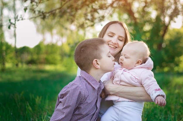 Junge mutter, ältester sohn und kleine tochter. bruder küsst kleine schwester. glückliches familienkonzept