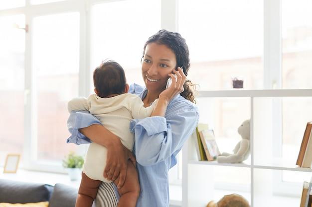 Junge mutter, die am telefon spricht, während sie baby hält