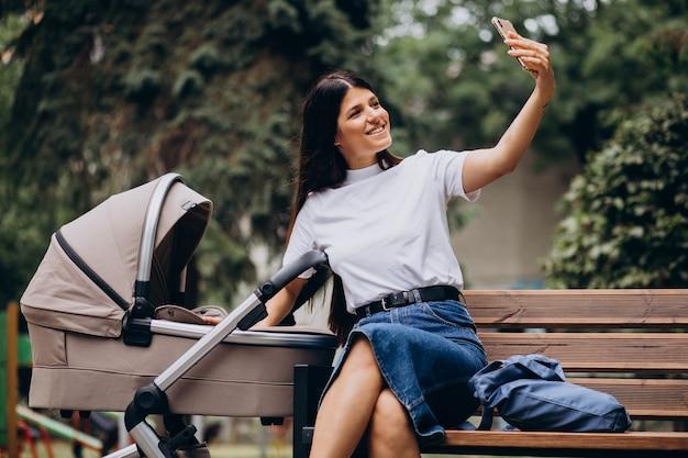 Junge mutter, die auf bank im park mit kinderwagen sitzt