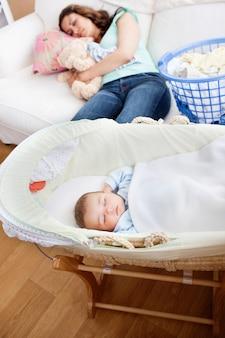 Junge mutter, die auf dem sofa schläft, während ihr baby in seiner wiege im wohnzimmer schläft