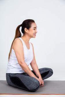 Junge mutter, die auf yogaauflage für übung sitzt