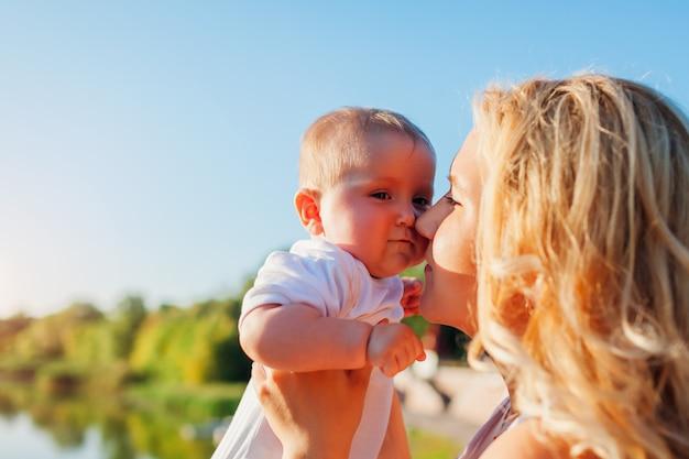 Junge mutter, die baby nah an ihrem gesicht hält. familie im park spazieren