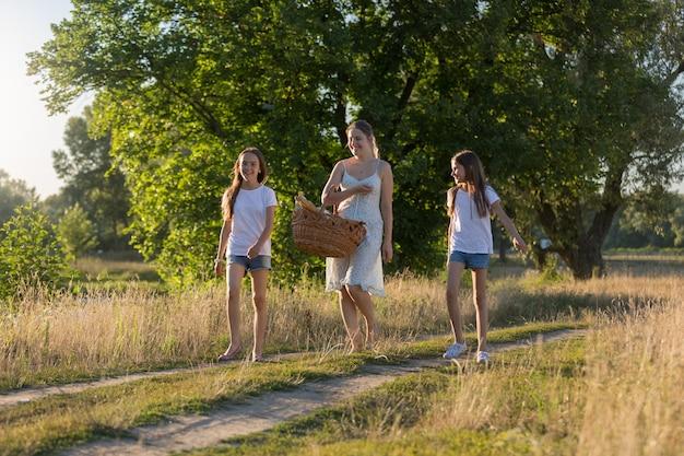 Junge mutter, die bei sonnenuntergang mit ihrer tochter auf der wiese geht