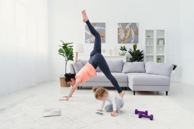 Junge mutter, die dehnübungen macht und yoga mit baby zu hause praktiziert. gesundheits- und sportkonzept.