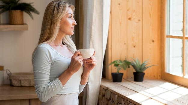 Junge mutter, die eine tasse kaffee genießt, während sie durch fenster schaut