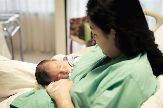 Junge mutter, die ihr neugeborenes baby hält, das erste lebenstage am krankenhaus schläft.