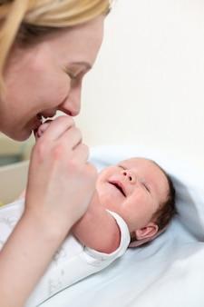 Junge mutter, die ihr neugeborenes kind umarmt. mutter stillendes baby. familie zu hause. liebes-, vertrauens- und zärtlichkeitskonzept.