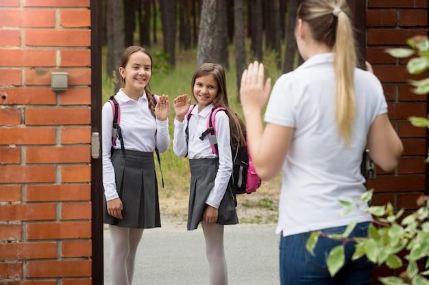 Junge mutter, die ihre beiden töchter zur schule bringt