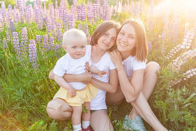 Junge mutter, die ihre kinder im freien umarmt. frau baby kind und teenager-mädchen sitzen auf sommerfeld mit blühenden wilden blumen grünen hintergrund