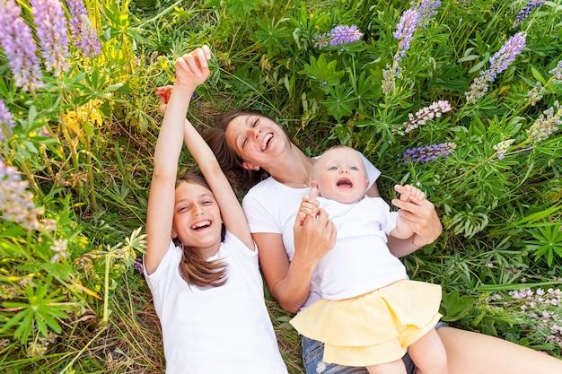 Junge mutter, die ihre kinder im freien umarmt. frauenbabykind und teenager-mädchen, die unten auf sommerfeld mit blühendem wildem blumengrünhintergrund liegen