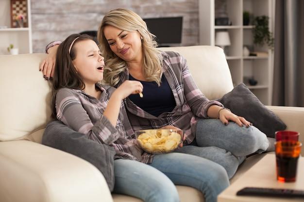 Junge mutter, die ihre tochter im teenageralter betrachtet, während sie auf dem sofa sitzt und fernsieht. glückliches kleines mädchen.