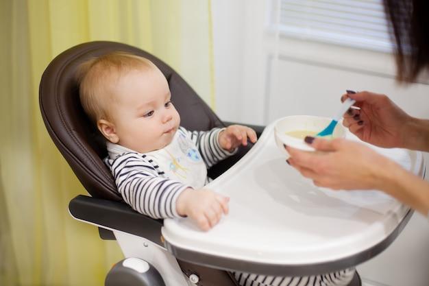 Junge mutter, die ihren kleinen babysohn mit brei füttert, die im hohen babystuhl sitzt
