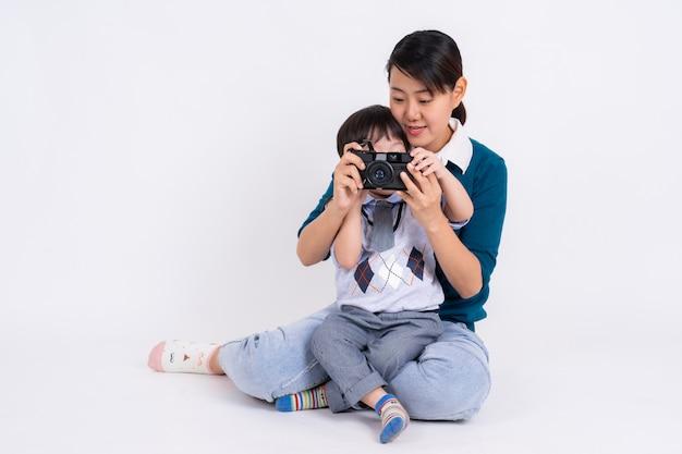 Junge mutter, die ihren sohn mit kamera auf weiß unterrichtet