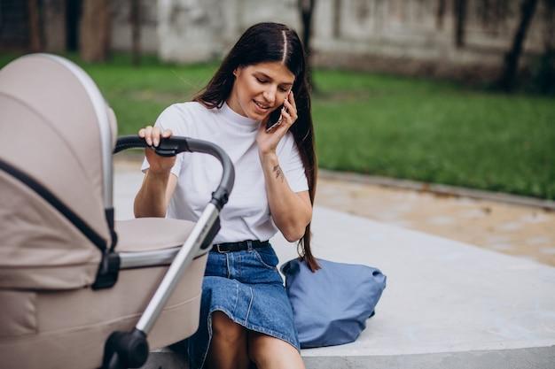 Junge mutter, die im park mit kinderwagen geht und am telefon spricht