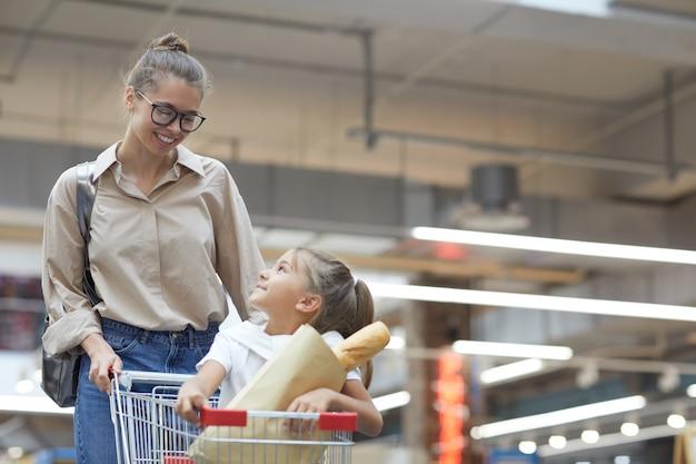Junge mutter, die im supermarkt einkauft