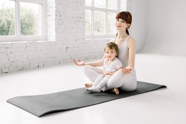 Junge mutter, die mit ihrem kleinen baby trainiert