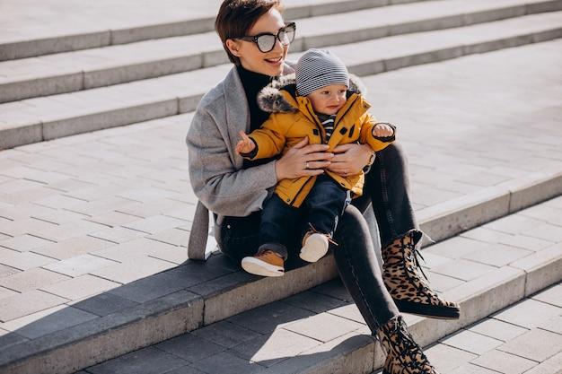 Junge mutter, die mit ihrem kleinen kleinkindsohn im park geht