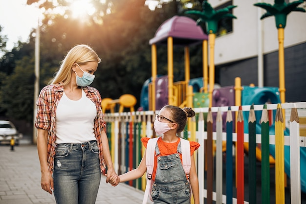 Junge mutter, die mit ihrer kleinen tochter auf der stadtstraße spaziert. sie tragen gesichtsschutzmasken. zurück zur schule und neues coronavirus-lifestyle-konzept.