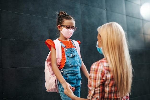 Junge mutter, die mit ihrer kleinen tochter zur grundschule geht. sie tragen gesichtsschutzmasken. zurück zum schulkonzept.