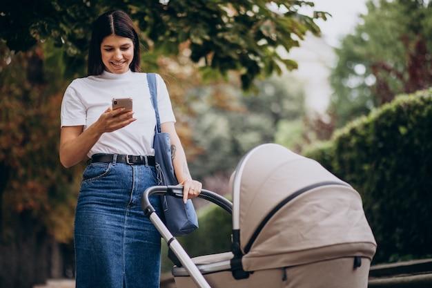 Junge mutter, die mit kinderwagen im park geht und am telefon spricht