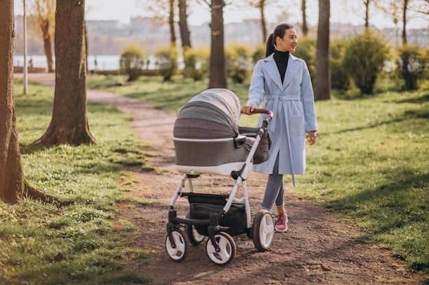 Junge mutter, die mit kinderwagen im park geht
