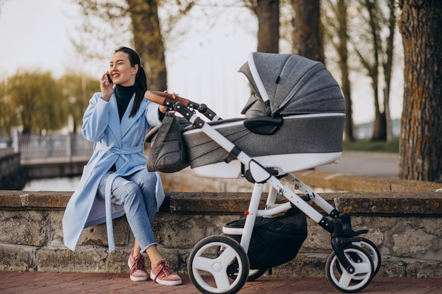 Junge mutter, die mit kinderwagen im park sitzt