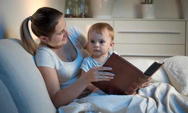 Junge mutter, die nachts mit ihrem baby im bett liegt und ein großes buch hält