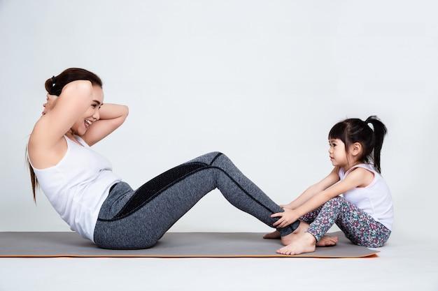 Junge mutter, die reizende tochter mit gymnastischem ausbildet