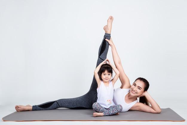 Junge mutter, die reizende tochter mit yoga ausbildet