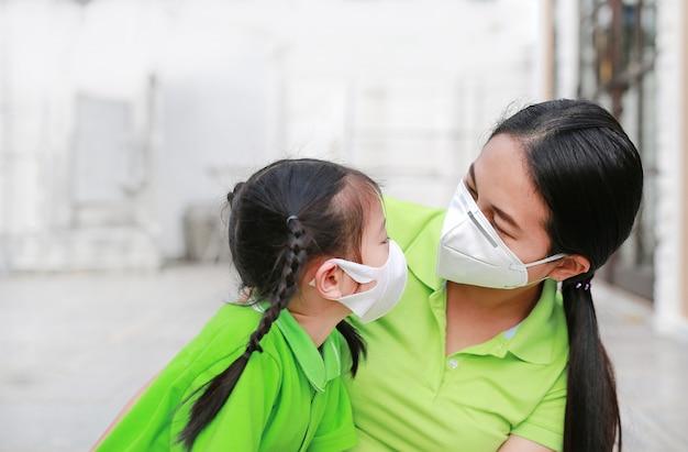 Junge mutter, die schutzmaske für ihre tochter während draußen zu luftverschmutzung in bangkok-stadt trägt