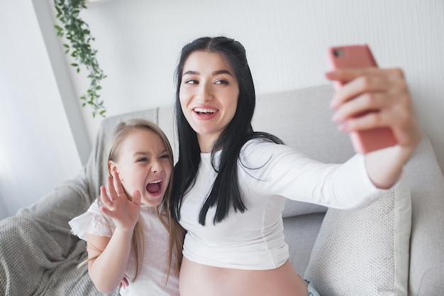 Junge mutter, die selfie mit ihrer kleinen tochter macht. frau erwartet baby. glückliche familie indoor.