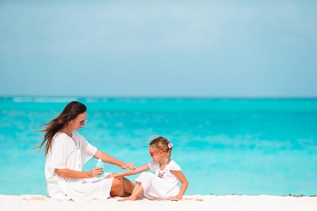 Junge mutter, die sonnencreme auf tochternase am strand anwendet. sonnenschutz